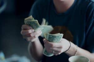 בחורה יושבת וסופרת כסף מאיתור כספים שביצעה