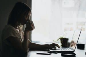 אישה בעבודה, יושבת מול לפטופ ושותה קפה